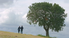 Husband and wife walking in field hand in hand, married couple together forever Arkistovideo