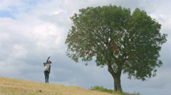 Happy young woman crazy dancing, jumping, waving hands, enjoying freedom in park Stock Footage