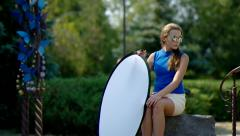 Girl in the park holds a reflector. Stock Footage