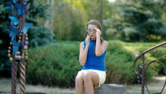 Teenager girl talking on the phone in the park. - stock footage