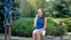 girl sitting on a stone dials a number on his cell. - stock footage