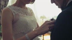 The bride fixing grooms buttonhole-flower slow motion Stock Footage