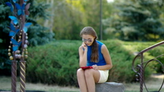 girl reads the e-book in the park. - stock footage
