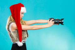 Photographer girl in santa claus hat shooting images - stock photo