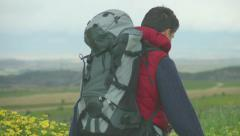 Young man wearing camping outfit and rucksack looking at mountains, traveling - stock footage