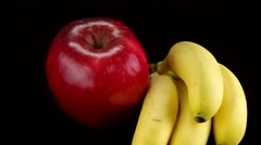 Red apple and bananas rotating with black background Stock Footage