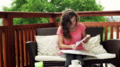 Occupied girl sitting on the deck and working on papers Stock Footage