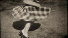 2453 - young girl spins aroung in her new plaid dress - vintage film home movie Stock Footage