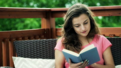 Stock Video Footage of Absorbed girl sitting on the deck and reading book