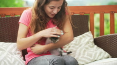 Girl playing with cute kitty on the terrace Stock Footage