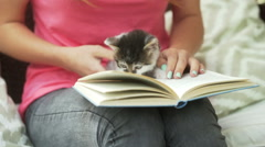 Girl holding kitty on her knees and reading book Stock Footage