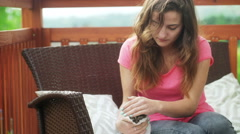 Girl sitting on the terrace and playing with little kitty Stock Footage