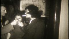 2449 - adults lighting cigarettes & smoking at home - vintage film home movie - stock footage