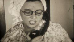 2455 - mom talks on vintage phone at home - vintage film home movie Stock Footage