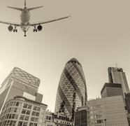 Aircraft landing in London passing over city buildings Stock Photos