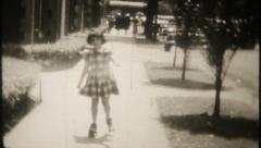 2459 - young girl roller skates on the sidewalk - vintage film home movie Stock Footage