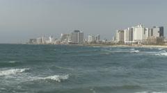 Tel Aviv skyline shore behind waves smashing in from the Mediterranean Sea - stock footage