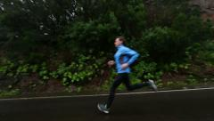 Jogging Sporty Man Running On Wet Country Road - STEADICAM Stock Footage