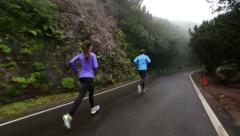 Man And Woman Running Jogging on Wet Country Road - STEADICAM TRACKING Stock Footage