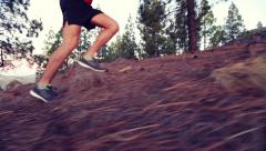 Running legs and shoes Of Man Jogging On Hill In Forest - STEADICAM Stock Footage