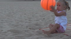 On the beach beautiful baby throws a big orange ball in the direction Stock Footage