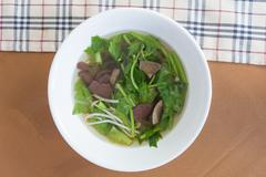Chinese clear soup with boiled entrails and vegetables. - stock photo