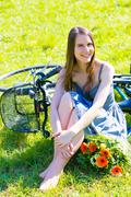 Young woman in short grey dress with long hair rides a bicycle with basket an Stock Photos
