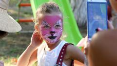 Body art painting on face of little girl on a family fest making photo via phone Stock Footage