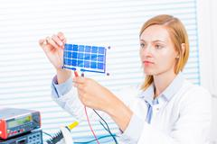 Woman laboratory assistant tests film  solar cells - stock photo