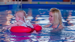 Mother teaching the baby how to swim Stock Footage