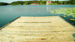 Woman in Shorts Walks On Wooden Pier, She Undressed Then Jumps In The Lake Stock Footage