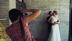 photographer takes pictures of newlyweds against the grey wall slow motion - stock footage