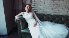Bride laying on a leather sofa slow motion Stock Footage