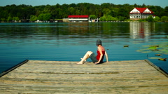 Girl With Sun Hat Dipping Her Feet In Lake And Looks Into The Distance Stock Footage