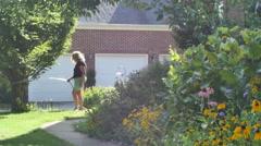 Woman gardening outside summer garden hose Stock Footage