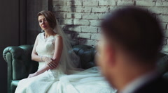 Bride sitting on a leather sofa and look at her groom slow motion Stock Footage