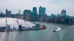 Tourist boat on River Thames, O2 arena and Canary Wharf district panoramic view  Stock Footage