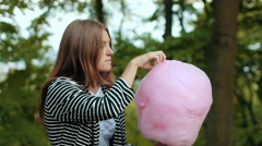 Stock Video Footage of Young woman eating cotton candy in park