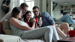 Friends watching something on smartphone and smiling to the camera Stock Footage
