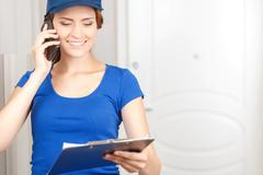 Delivery woman talking on mobile phone Stock Photos