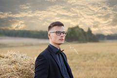 Young man with glasses thinking and standing on the field - stock photo