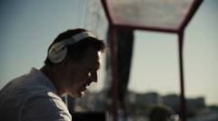 DJ in white headphones playing on turntables Stock Footage