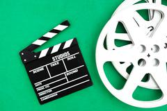 Movie clapper board and reel green background Stock Photos