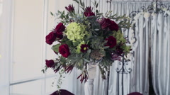 Bouquet of flowers as a decoration of a round festive table at a restaurant Stock Footage