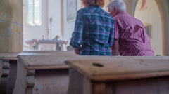 Two Christians crossing themselves and sitting in pew - stock footage