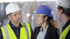 4k female engineer or architect discussing construction with male colleagues - stock footage