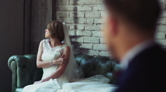 Bride sitting on a leather sofa groom looking at her slow motion Stock Footage