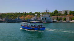 Pleasure boat passes by warships moored in the bay. - stock footage