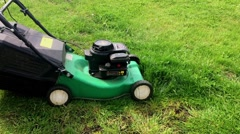 Girl cleans the yard, mows the lawn mower. Stock Footage