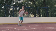 The young man playing street basketball on the court Stock Footage